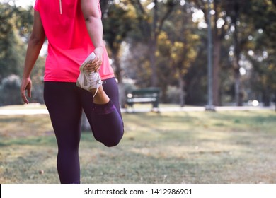 Sport woman stretching leg muscle preparing for running in the public park outdoor. Close up of female athlete lower body doing legs stretches getting ready for cardio warmup.