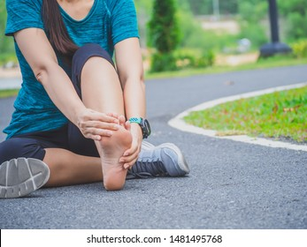Sport woman suffering from pain in ankle while sitting on street in garden.