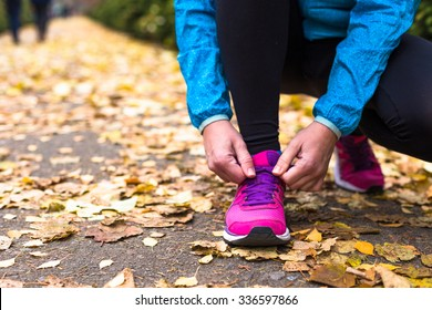 Sport woman tying running shoes during outdoor cross training workout. Beautiful young and fitness sport model training outside.