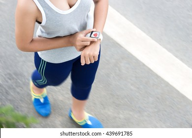 sport woman use digital hand watch checking health application on road
