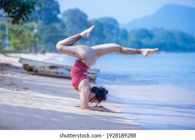 Sport woman yogini scorpion pose practice yoga exercise on the beach sea in relaxing day , yoga is meditation and healthy sport concept