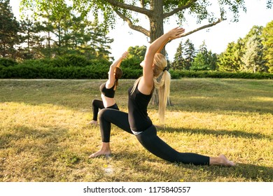 Sport women doing yoga outside in morning. Fitness girls relax in park.
