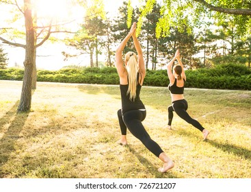 Sport women doing yoga outside in morning. Fitness girls relax in park
