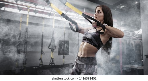 Sport. Women training with fitness trx straps in the gym. Beautiful lady exercising her muscles sling or suspension straps.