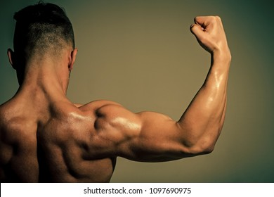 Sport and workout. Athletic bodybuilder man on grey background. Dieting and fitness, healthy lifestyle. Coach sportsman showing biceps and triceps. Man with muscular wet body and back.