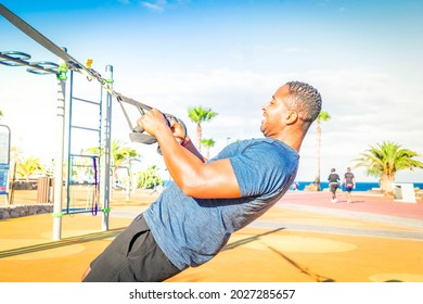 Sport workout of happy african american men making trx training on outdoor sports gound