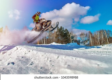 Sport yellow snowmobile jump. Cloud of snow dust from under snowmobile tracks. Concept quick movement. Extreme sport background for any purposes. Copy space.