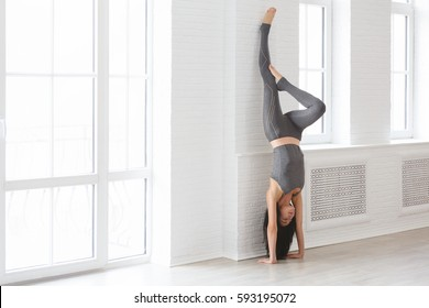 Sport and yoga. Strong young athletic woman doing exercise -Handstand against an picture window on black mat, full length