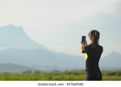 Sport young Asian woman runner taking picture using smartphone while doing running exercise at outdoor. Concept modern young active lifestyle.