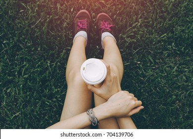 Sport young asian woman sitting on grass, drinking coffee. Resting Runner. Vintage filter.