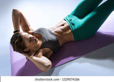 Sport. Young fit woman working out with abdominal muscles in a gym. Isolated.