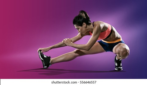Sport. Young woman stretching her leg.