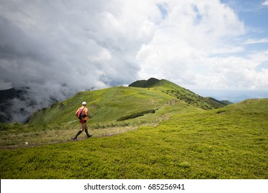 sporting man with compress socks and hiking poles running on high mountain trail before summer rainy storm