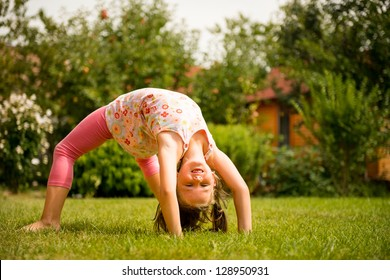Sporting on grass - smiling little child making bridge outdoor in backyard