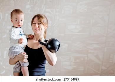 Sportive beautiful mother with baby and kettlebell in hands. Motherhood is not a cause to let oneself go