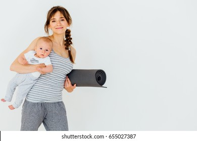 Sportive beautiful mother with baby and yoga mat in hands. Motherhood is not a cause to let oneself not be athletic and healthy. Fitness, happy maternity and healthy lifestyle concept.