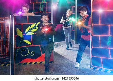 sportive boy aiming laser gun at other players during lasertag game in dark room