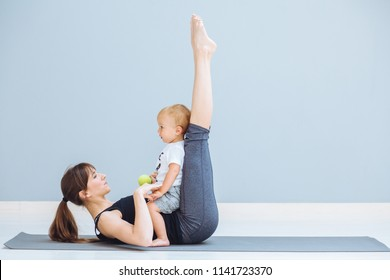 Sportive brunette mother with baby son doing press exercise on grey yoga mat over gray wall background. Athletic and healthy motherhood. Fitness, happy maternity and healthy lifestyle concept.