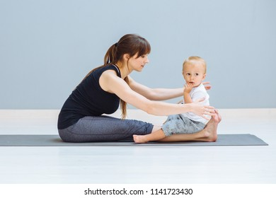 Sportive brunette mother with baby son relax after good workout on grey yoga mat over gray wall background. Athletic and healthy motherhood. Fitness, happy maternity and healthy lifestyle concept.