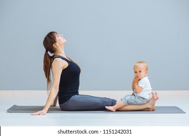 Sportive brunette mother doing stretching, workout together on yoga mat over gray wall background. Athletic and healthy motherhood. Fitness, happy maternity yoga with children concept.
