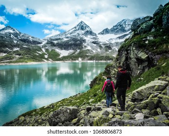 sportive couple hiking in a dreamlike mountain scenery in the european alps with view of a glacier lake