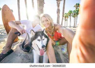 Sportive couple with husky taking a selfie with smartphone - Two friends smilingand having fun while resting in the shadow of palm trees on a tropical beach