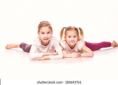 Sportive cute little girls lying on a floor isolated over white