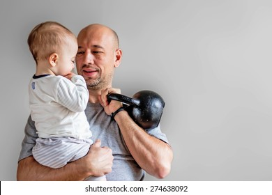 Sportive dad with his son and kettlebell in hands. Image with blur grey background