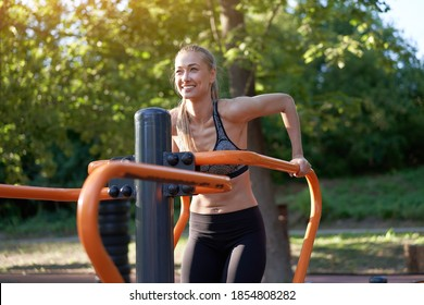 Sportive female training dip exercise machine outdoor gym summer park Middle age caucasian woman dressed sportswear workout outside on simulator sport ground. Healthy lifestyle concept
