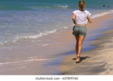 Sportive Girl is running along the beach of the ocean for keeping the perfect body in order