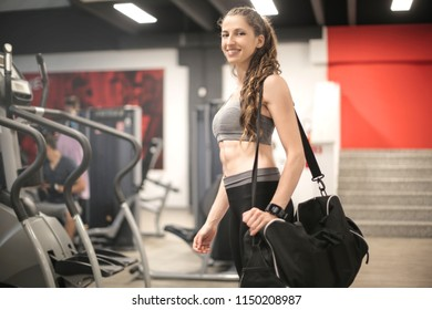 Sportive girl walking in the gym with a bag