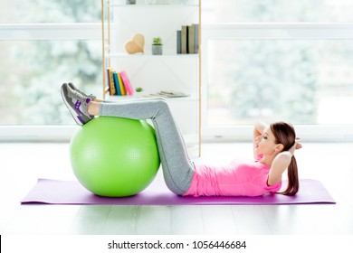 Sportive lifestyle endurance concept. Profile side photo of charming beautiful sporty sexy girl wearing tight leggings and pink casual tshirt outfit doing crunches using green fitness ball