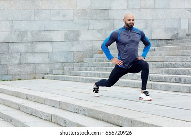 Sportive man exercising between staircases in the city