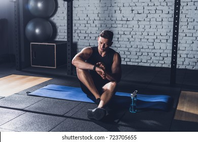 sportive man looking at smartwatch while sitting on mat in gym