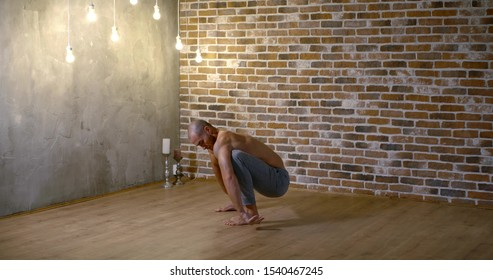 sportive man is meditating in yoga asanas in home, squatting and standing on legs