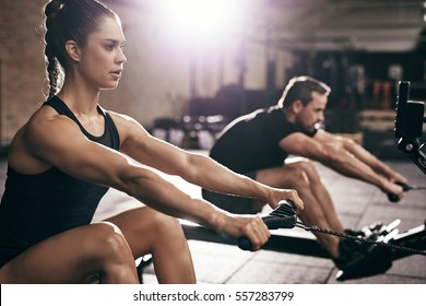 Sportive man and woman doing cardio training in gym. Horizontal indoors shot
