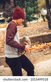 Sportive man working out and training muscles while carrying piece of stone in park.