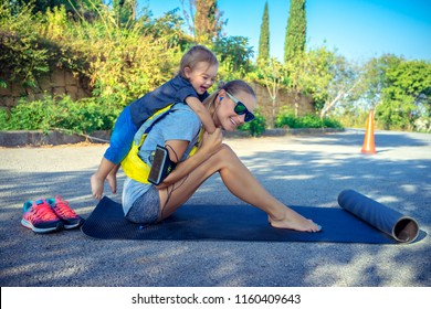 Sportive mother with child outdoors doing fitness excercise,  happy family together on workout, active healthy lifestyle