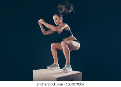 Sportive muscular lady working out standing on wooden box ready to jump isolated over black background