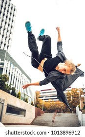 Sportive parkour athlete flying and flipping above ground on street.