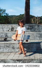 Sportive preschool asian girl dressed in casual clothing holds her skateboard and poses in the park in Thailand. Summertime vacations.