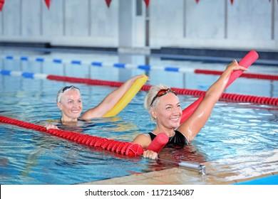 Sportive senior women doing exercises in indoor swimming pool