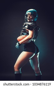 Sportive serious woman in helmet of rugby player holding ball in stuio on dark background. Back view.
