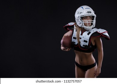 Sportive serious woman in helmet of rugby player holding ball in stuio on dark background. . Copy space