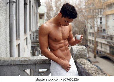 A sportive, sexy, attractive naked young man in bathroom towel, standing with cup of coffee on the balcony. Horizontal view, isolated on street background.