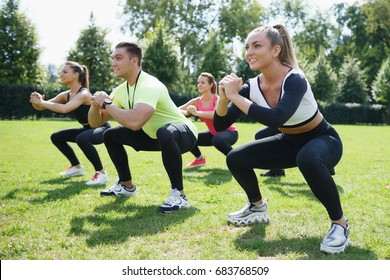 Sportive and smiley. Group of athletic young women in sportswear doing physical exercises  with male coach in green summer park.  Sport outdoors
