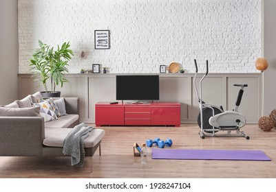 Sportive and training room interior style with purple mat blue dumbbell and bike style. Grey sofa white brick wall frame and television concept.