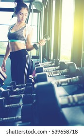 Sportive woman choosing her weight dumbbells in gym. color tone.