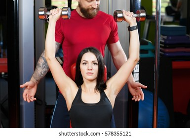 Sportive woman doing chest and shoulder exercises with dumbbells on the bench at gym while her personal coach assisting her and giving instructions