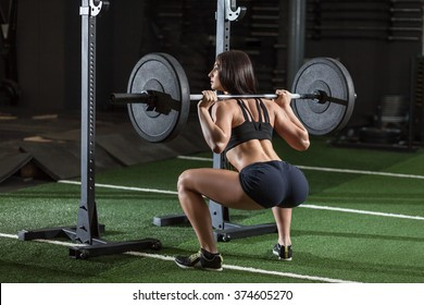Sportive woman doing squatting with a barbell at the gym
